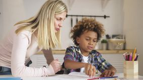 Il bambino creativo ed astuto sta sedendosi allo scrittorio ed al compito di disegno della scuola stock footage