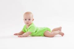 Il bambino curioso sveglio si trova sul suo stomaco e sull'esame della macchina fotografica fotografia stock