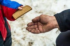 Il bambino dà all'uomo un il pezzo di pane di segale Immagine Stock Libera da Diritti