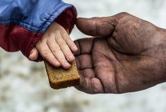 Il bambino dà all'uomo un il pezzo di pane di segale Immagini Stock Libere da Diritti