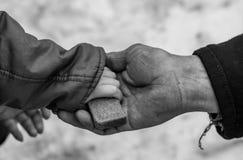 Il bambino dà all'uomo un il pezzo di pane di segale Fotografie Stock Libere da Diritti