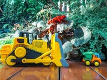 Il bambino dei bambini gioca il trattore ed il camion sul pavimento di legno nel campo da giuoco Immagini Stock Libere da Diritti