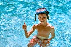 Il bambino del bambino del ragazzo otto anni dentro gli occhiali di protezione luminosi di immersione subacquea del giorno di div Fotografia Stock
