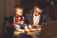 Il bambino del figlio e del padre lavora a casa al computer nello scuro fotografie stock