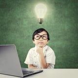 Il bambino del genio con il computer portatile pensa l'idea sotto la lampada Fotografia Stock
