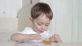 Il bambino del ragazzo beve l'acqua da un vetro video d archivio