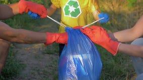 Il bambino dell'attivista aiuta la mamma ed il papà a raccogliere l'immondizia nella borsa di rifiuti mentre libera la natura dal video d archivio