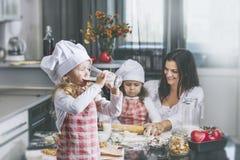 Il bambino della bambina beve il latte con la sue madre e sorella c felice immagine stock libera da diritti