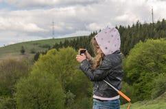 Il bambino della bambina prende le immagini sul telefono della montagna mentre viaggia immagine stock