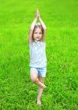 Il bambino della bambina sull'erba fa l'esercizio di yoga all'aperto Fotografia Stock