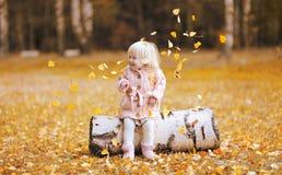 Il bambino della foto di stile di vita di autunno getta sulle foglie e divertiresi Fotografia Stock Libera da Diritti