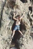 Il bambino della ragazza all'aperto scala l'albero con la pittura del fronte della farfalla Fotografie Stock