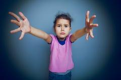 Il bambino della ragazza chiede le mani sull'incrocio grigio del fondo Immagine Stock