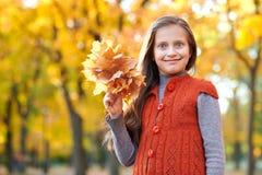 Il bambino della ragazza con le foglie gialle è nel parco della città di autunno Alberi gialli luminosi immagine stock libera da diritti