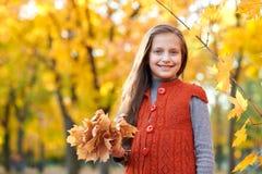 Il bambino della ragazza con le foglie gialle è nel parco della città di autunno Alberi gialli luminosi fotografia stock
