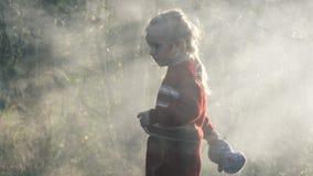 Il bambino della ragazza estingue il fuoco stock footage