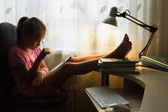 Il bambino della ragazza impara a casa Fotografia Stock
