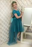 Il bambino della ragazza nel vestito affascinante che sta accanto allo specchio, pieno d'ammirazione Fotografia Stock Libera da Diritti
