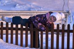 Il bambino della ragazza scala il recinto Il tempo di divertimento è infanzia Sera piena di sole di inverno Tramonto Fotografia Stock