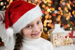 Il bambino della ragazza si è vestito in cappello di Santa con i regali di natale sul concetto della celebrazione del fondo illum Fotografia Stock Libera da Diritti