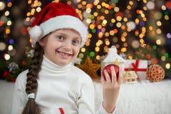 Il bambino della ragazza si è vestito in cappello di Santa con i regali di natale sul concetto della celebrazione del fondo illum Immagine Stock