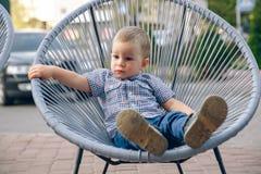 Il bambino dello zenzero si è vestito in jeans e maglietta blu che si siedono sull'aria aperta in sedia di vimini Fotografie Stock