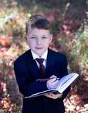 Il bambino di affari sulla natura fa le note in un taccuino Fotografia Stock Libera da Diritti