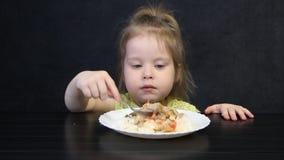 Il bambino di 3 anni mangia il riso ed i funghi cucinati con un cucchiaio su un fondo nero alla tavola nera archivi video
