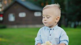 Il bambino di 1 anno allegro sta mangiando una banana ` s che sta sul retro della casa stock footage