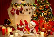 Il bambino di Natale redige la lista di obiettivi, il bambino Santa Hat Writing Letter Fotografie Stock