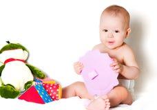 Il bambino di seduta con i giocattoli Fotografia Stock