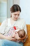 Il bambino di tre mesi succhia il seno Immagine Stock
