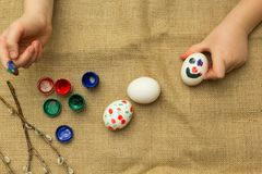 Il bambino dipinge le uova per Pasqua illustrazione di stock
