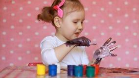 Il bambino divertente dipinge le sue mani con pittura La bambina dell'artista del bambino disegna l'arte stock footage