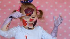 Il bambino divertente dipinge il suoi viso e mani con pittura la bambina sporca dell'artista disegna il trucco video d archivio