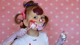 Il bambino divertente dipinge il suoi viso e mani con pittura la bambina sporca dell'artista disegna il trucco stock footage