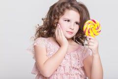 Il bambino divertente mangia la lecca-lecca della caramella, bambina che mangia i dolci, studio Immagine Stock