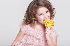 Il bambino divertente mangia la lecca-lecca della caramella, bambina che mangia i dolci, studio Fotografia Stock Libera da Diritti