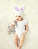 Il bambino dolce felice in cappello tricottato con le orecchie di coniglio e l'orsacchiotto riguardano il letto Fotografie Stock