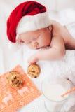 Il bambino dorme in un cappello di Santa Claus Immagine Stock