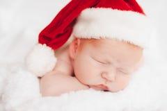 Il bambino dorme in un cappello di Santa Claus Fotografia Stock