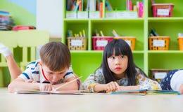 Il bambino due indica sul libro di racconto della lettura e del pavimento nel movimento di liberazione prescolare Immagine Stock