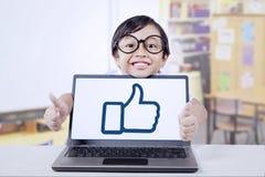 Il bambino e la a gradiscono l'icona sul computer portatile Immagini Stock