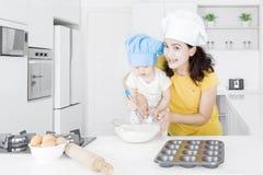 Il bambino e la madre fanno il dolce immagini stock