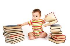 Il bambino e un mucchio dei libri Fotografie Stock Libere da Diritti