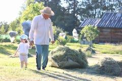 Il bambino ed il nonno hanno raccolto il fieno Fotografia Stock