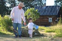 Il bambino ed il nonno hanno raccolto il fieno Immagine Stock