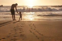 Il bambino ed il padre sono alla spiaggia. Fotografia Stock