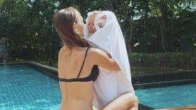 Il bambino esaurisce la piscina a sua madre che aspettandola con un asciugamano video d archivio