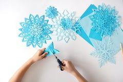 Il bambino fa i fiocchi di neve di carta blu Immagini Stock Libere da Diritti